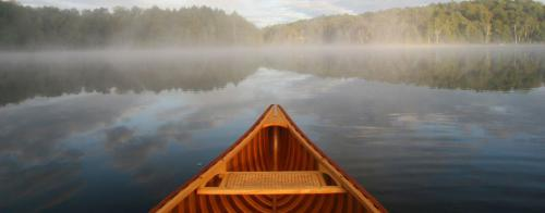 Front of a canoe facing a misty lake