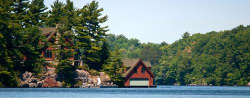 A lakeside cottage partially covered by tall Pine Trees