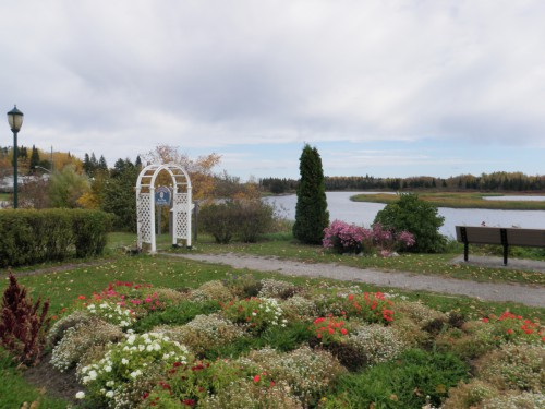 Walking trail with a beautiful view of a floral garden and lake