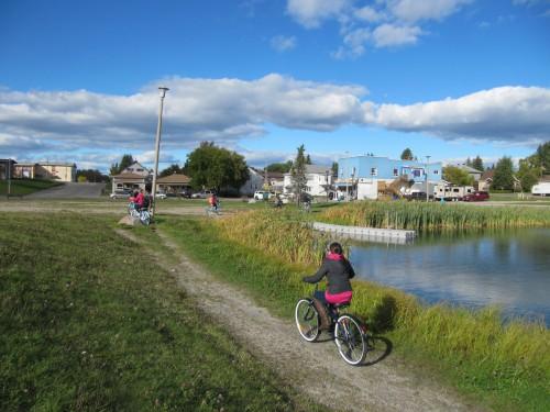 People biking on a trail by a lake