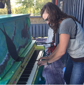 An individual playing on an outdoor piano