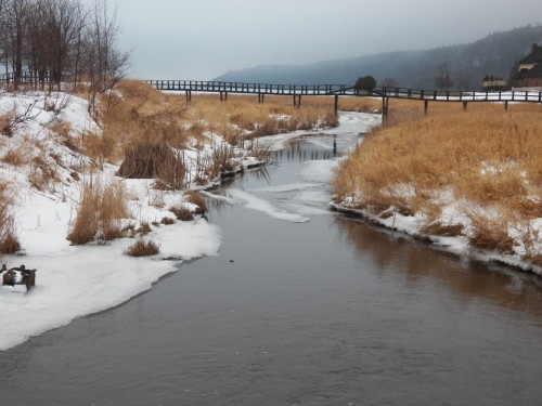 Winter view of the river embankment featuring a bridge