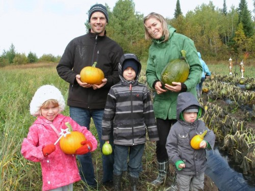 A mother, father, and three children pose with pumpkins grown in a pumpkin patch