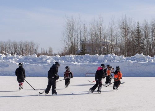 A group of children playing ice hockey on an outdoor rink in the winter