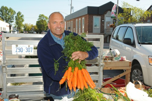 A man proudly displaying his locally grown produce at the farmers market