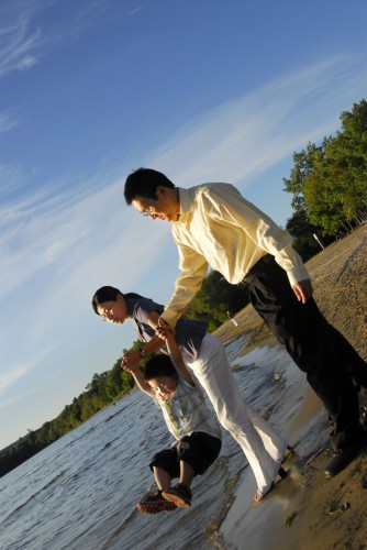 A mother and father playing with their child on a sandy lake shore