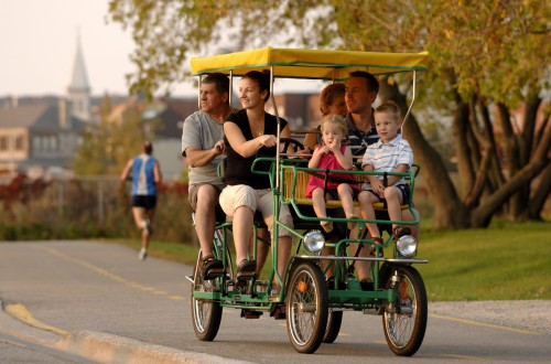 A family of six on a carriage bike, biking through the streets