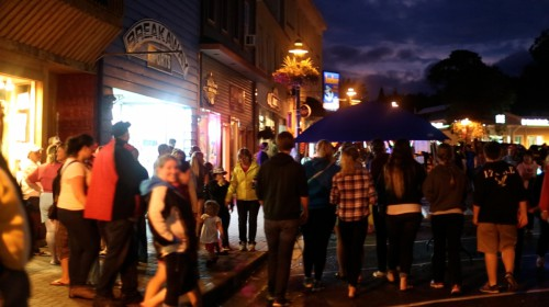 Many people walking through downtown event in the evening
