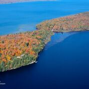 Aerial view of fall foliage surrounded by crystal blue water
