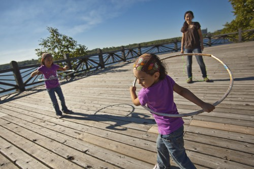 Two young girls being supervised as they play with hoola-hoops on a large wooden platform