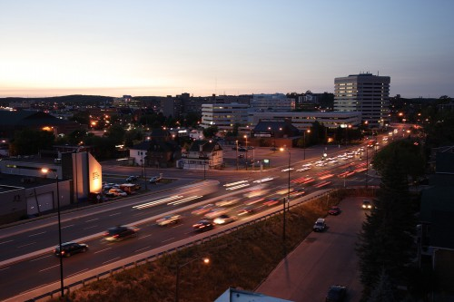 View of the city at dusk with traffic on the main highway