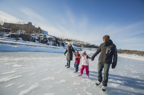 Two adults skating with two young girls, smiling and laughing